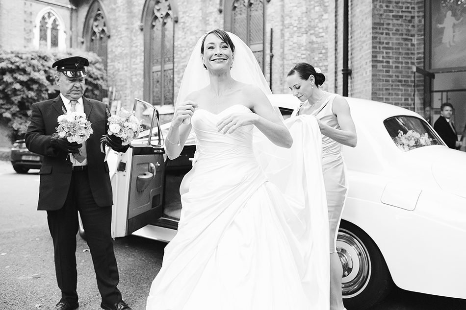 photograph of bride getting out of car on wedding day