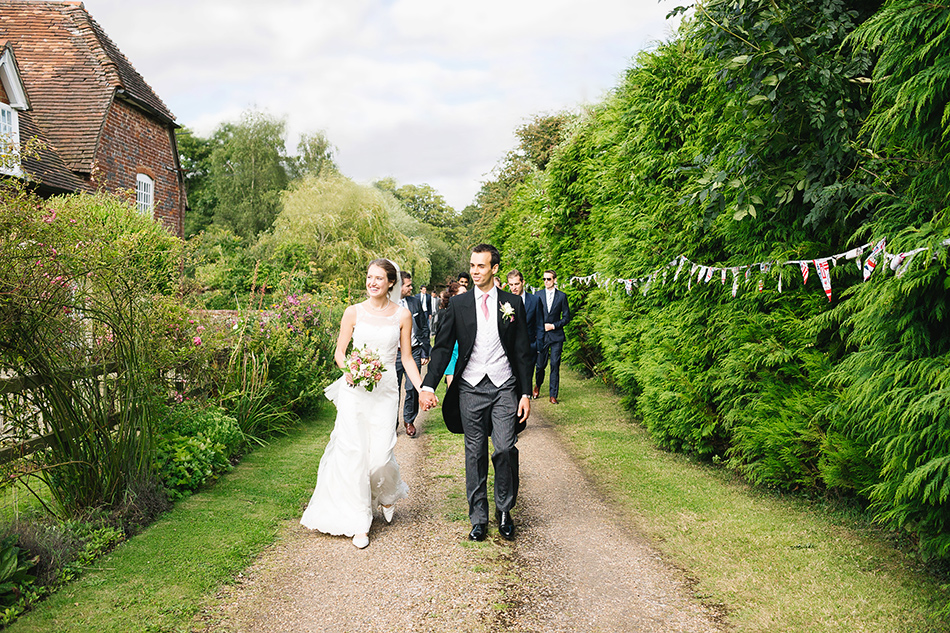 bride and groom wedding photographer walking with guests