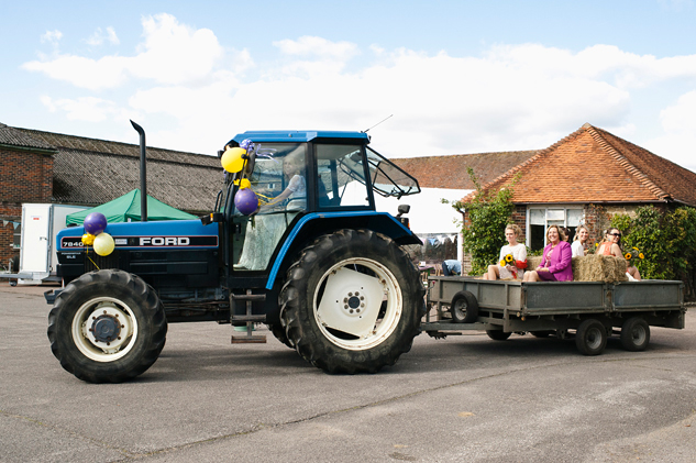 bride arriving on tractor at farm wedding