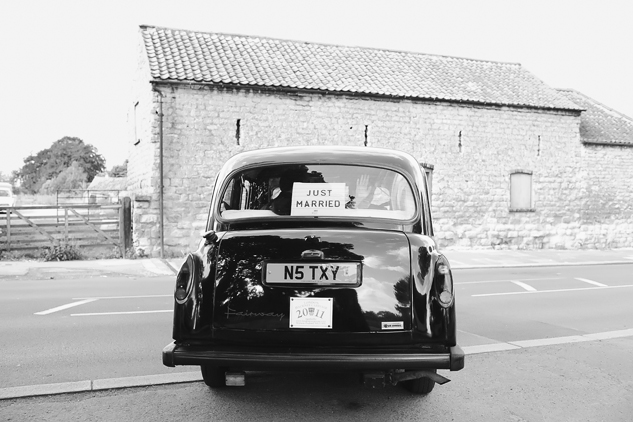 black and white wedding photo of black taxi bride and groom leaving just married sign